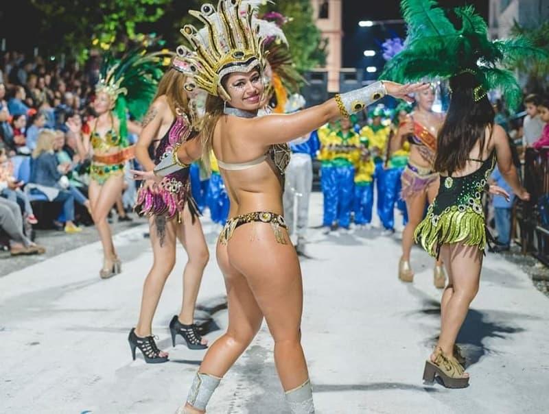 Una mujer con disfraz de carnaval baila y sonríe mientras desfila; detrás se observan más personas desfilando