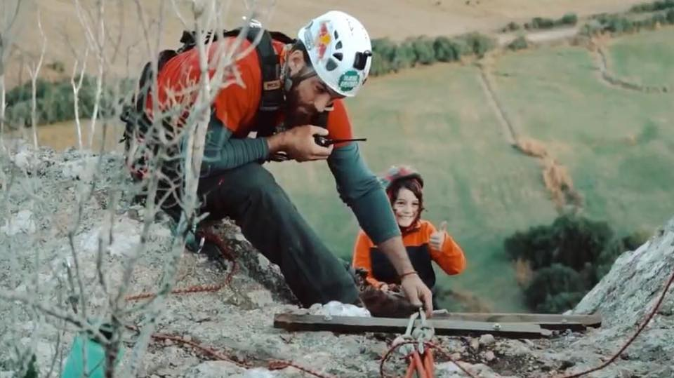 Un niño sonriente comienza el descenso en rapel por una alta pared de piedra, mientras un hombre a pocos metros de él verifica los implementos de seguridad y habla por un equipo de radio