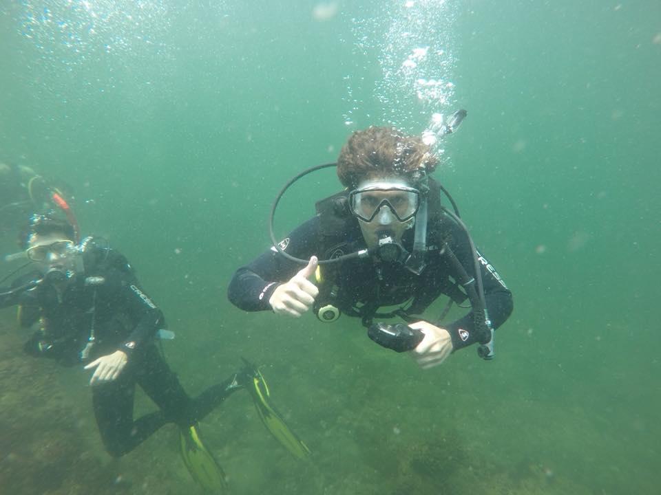 Imagen de dos personas buceando bajo el océano; uno de ellos levanta el pulgar a la cámara