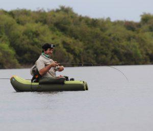 Imagen de un hombre sobre un pequeño elemento de flotación pescando en medio de un río angosto; al fondo se observa un monte nativo