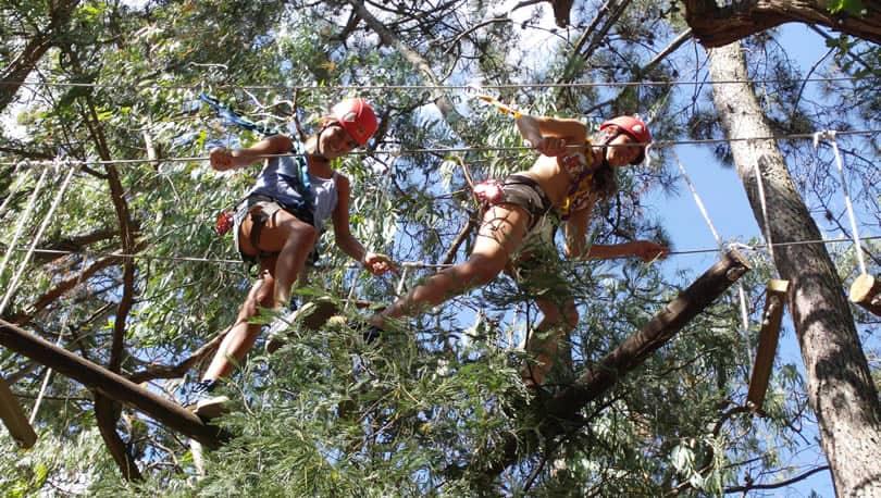Dos mujeres adolescentes sonrientes caminan sobre cuerdas en entre los árboles