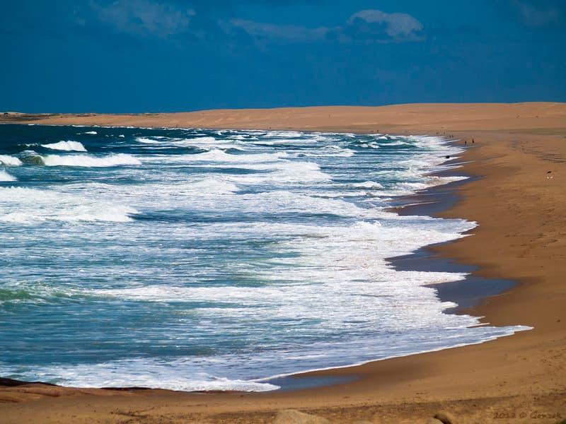Vista de la playa de Cabo Polonia, uno de los parques nacionales de Uruguay; una extensa franja de dunas de arena se extiende frente al mar.