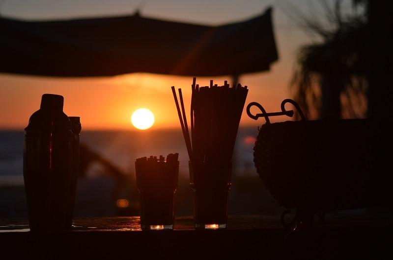 Imagen del sol cayendo sobre el océano; delante hay una coctelera y dos vasos con tragos