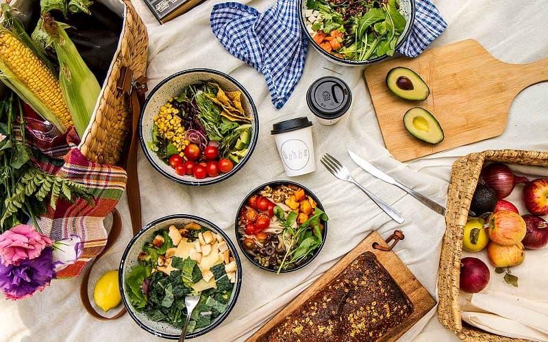 En una mesa, varios bowls con ensaladas distintas, alrededor de las cuales hay tablas, verduras, y panes