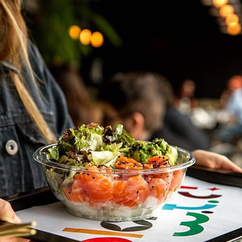 Una mujer sostiene una bandeja sobre la que hay un bowl con ensalada