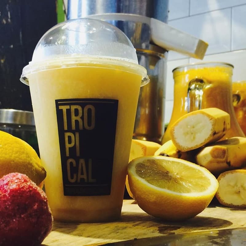 Un vaso plástico con un licuado de frutas amarillas, rodeado de diversas frutas