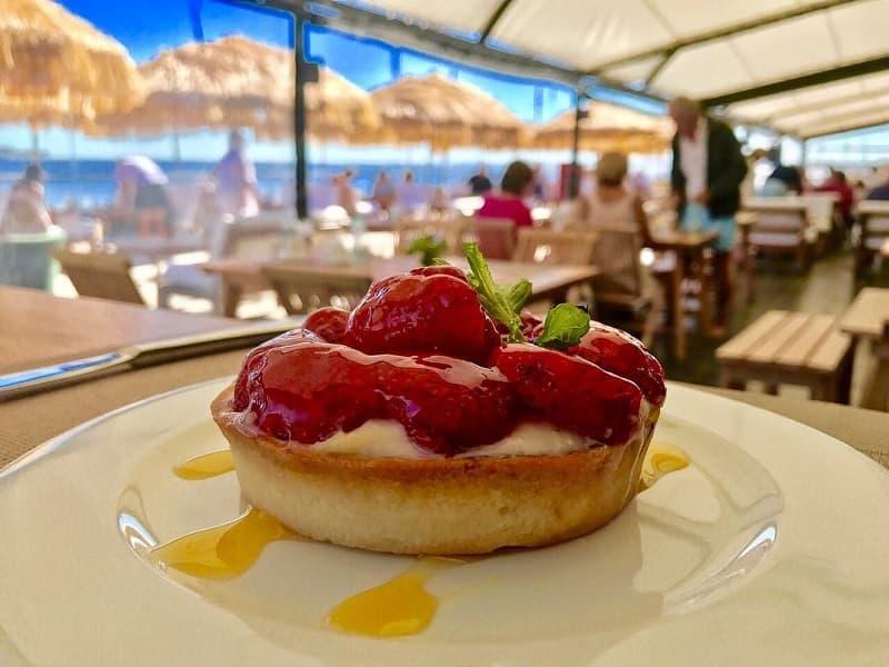Imagen de una cheesecake de frutilla, sobre un plato blanco; al fondo se observan mesas y personas almorzando en restaurante de Punta del Este donde ofrecen descuentos con tarjetas