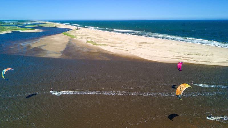 Toma aérea muestar a varios turitas haciendo kite surf en Laguna Garzón, cerca de José Ignacio