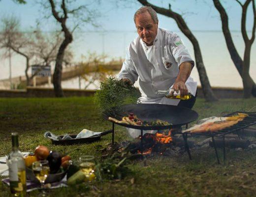 Un cheff prepara un plato sobre una gran sartén en un espacio abierto frente al Río Uruguay