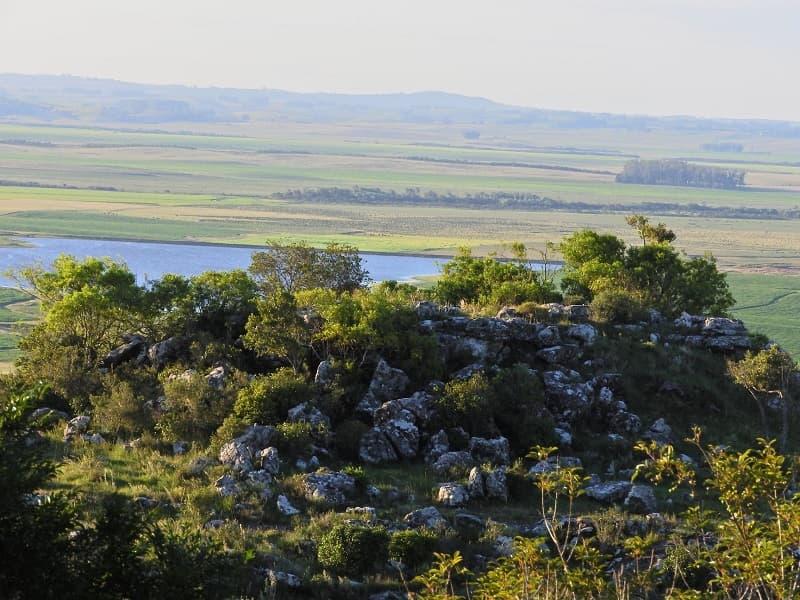 Vista desde la cima de un cerro de un paisaje de sierras verde, con un lago al centro, en Paso Centurión, uno de los parques nacionales de Uruguay