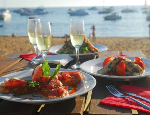 tres platos con frutos del mar y tres copas de champagne sobre una mesa, frente al puerto de Punta del Este