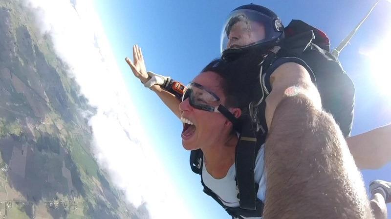 Una mujer grita mientras cae en caída libre en un salto en paracaidas tandem