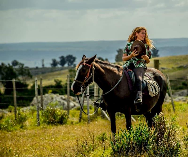 Una mujer cabalgando, sosteniendo un sombrero de ala entre sus manos; al fondo, un paisaje de sierras
