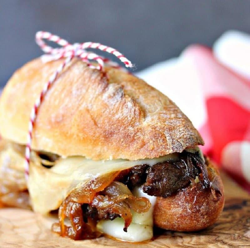 Un chivito de lomo con queso y panceta, entre dos panes caseros atados por un piolín rojo y blanco.