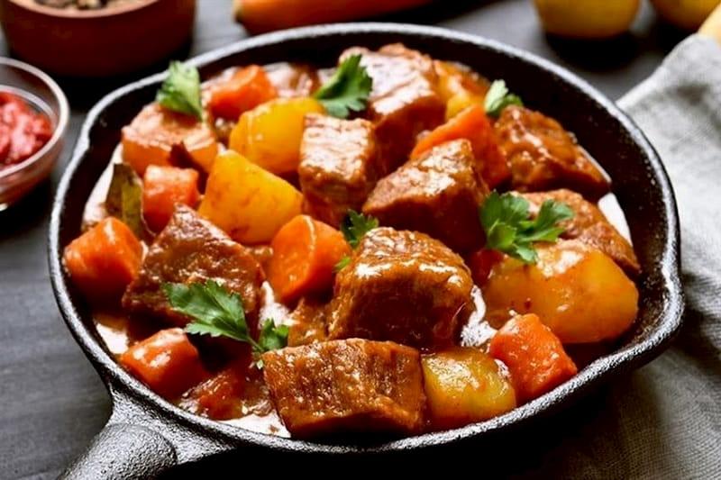 Un plato con cubos de carne, y verduras.