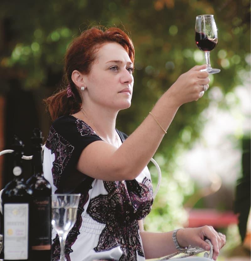 Una mujer levanta una copa con vino tinto; a su costado hay una botella de vino y una copa de agua