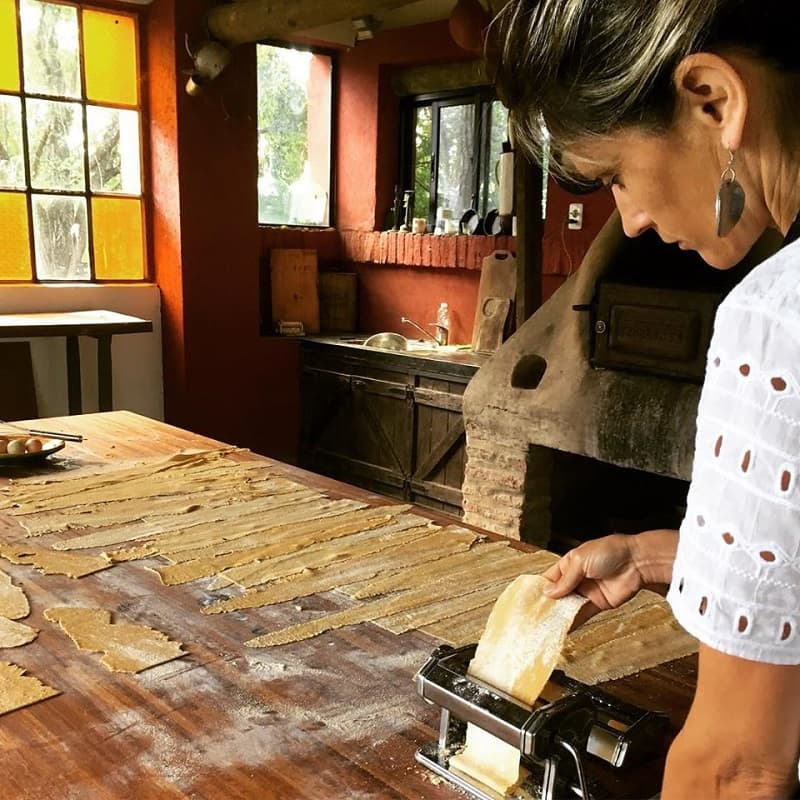 Una mujer elabora pasta artesanal sobre una mesada de madera