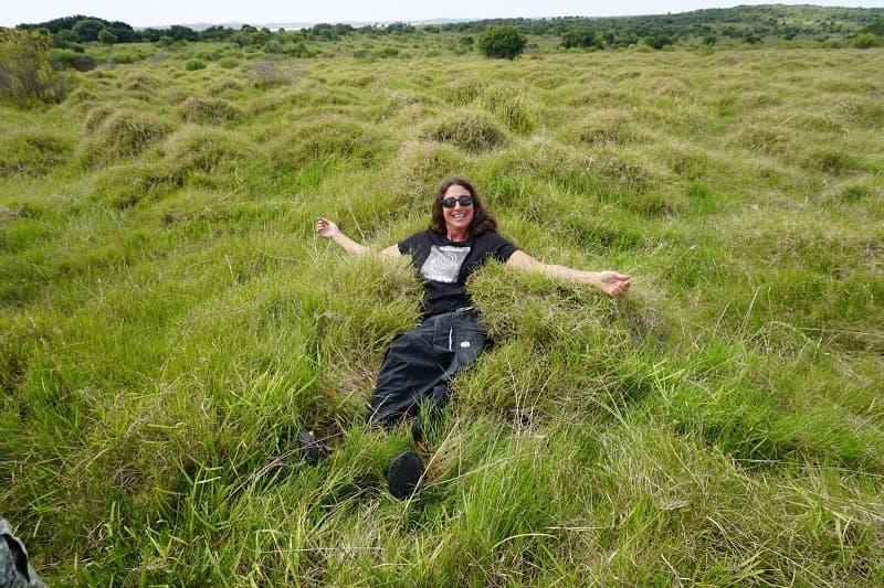 Una mujer, sonriente, acostada sobre un campo verde