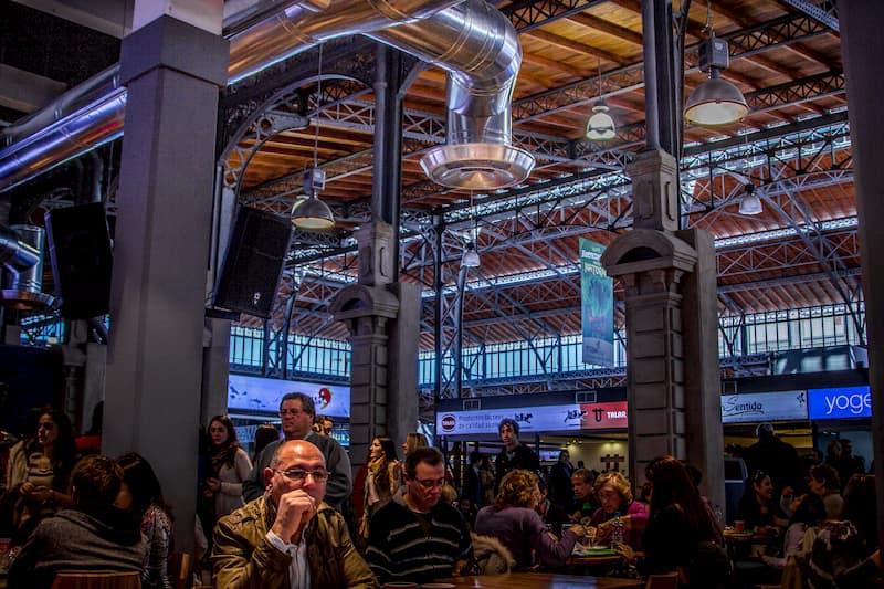 Varias personas cenando en mesas, dentto de un espacio de techos muy altos con ventanales y estructuras de hierro