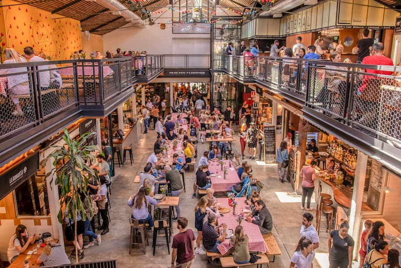 Plano general desde arriba del interior Mercado Ferrando; muchas personas sentadas en mesas