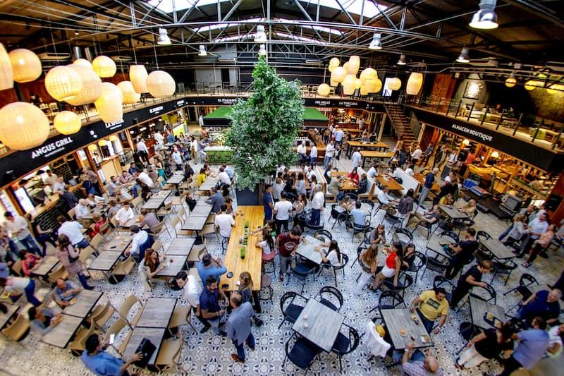 Muchas personas sentadas en un gran espacio cerrado; en el techo hay luces envueltas en globos blancos de papel