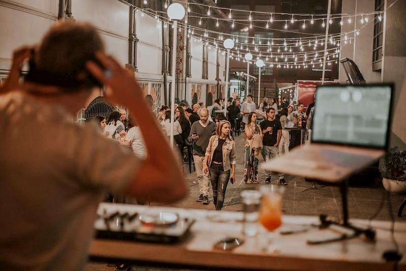 Varias personas caminan y otras están sentadas en mesas, sobre un callejón, frente a un DJ que pone música