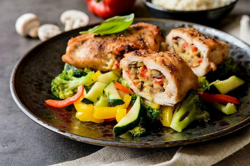 Un plato de pollo relleno, sobre una base de verduras al vapor